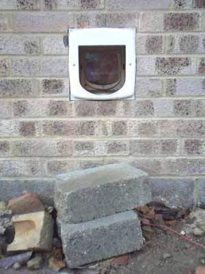A cat door installed in a brick wall